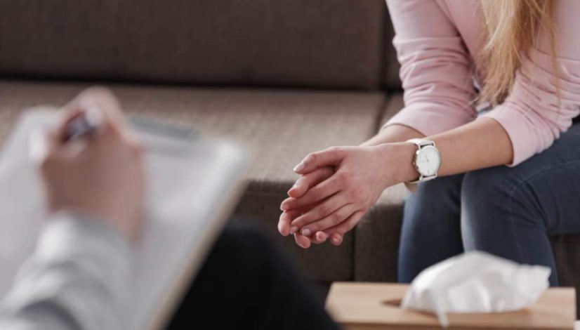 Close-up of woman's hands during counseling meeting with a professional therapist. Box of tissues and a hand of counselor blurred in the front.