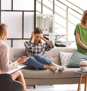 Young woman and her teenage daughter visiting child psychologist in office